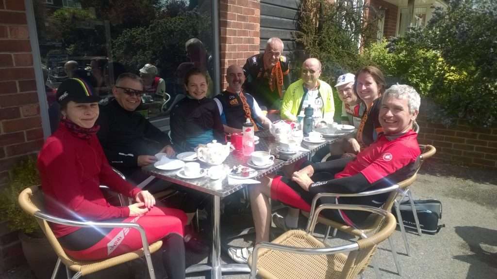Photo of eight cyclists having coffee and cakes